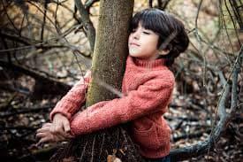 Niño feliz abraza un árbol dentro de un bosque, buen entorno para vivir el inglés.